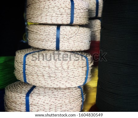 Coiled rope at a fishing shop for fishing industry. A collection of  coiled rope. White coiled ropes, black coiled rope.