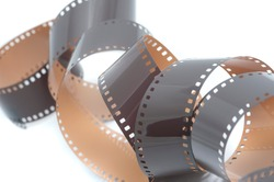 Coiled spiral of old 35mm film negatives with developed frames and sockets on a white background in a photography concept