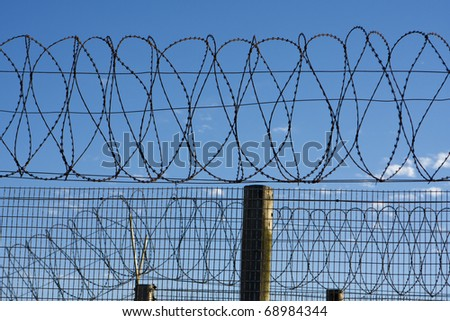 Coils of barbed wire atop a fence provide security at a penitentiary in South Africa. The barb wire symbolizes protection and security -- but also the freedom beyond the perimeter of the prison walls.
