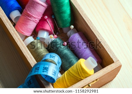 coils of multi-colored threads, pins and a centimeter tape in a wooden box, a hobby, a tailor, handicrafts #1158292981
