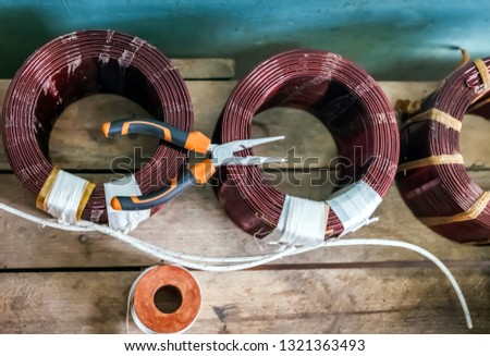 Coils without copper wire frames and pliers close-up on the background of boards #1321363493