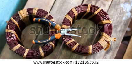 Coils without copper wire frames and pliers close-up on the background of boards #1321363502