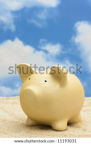 Coin bank on sand – savings for vacation or retirement
