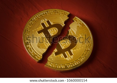 Coin bitcoin is broken in half on red background. The fall and collapse of the course of the crypto currency, the ban on trade, fall down
