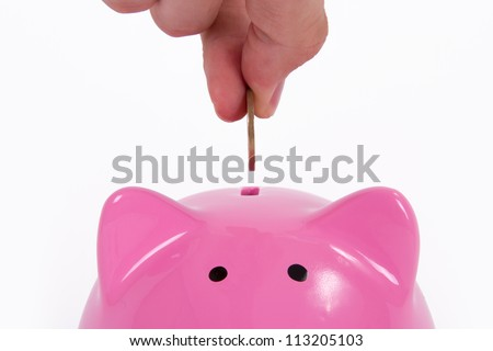 Coin holding by a human hand, fingers and pink piggy bank, isolated on white background.