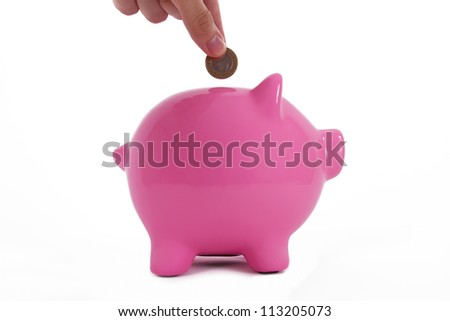Coin holding by a human hand, fingers and pink piggy bank standing, isolated on white background.