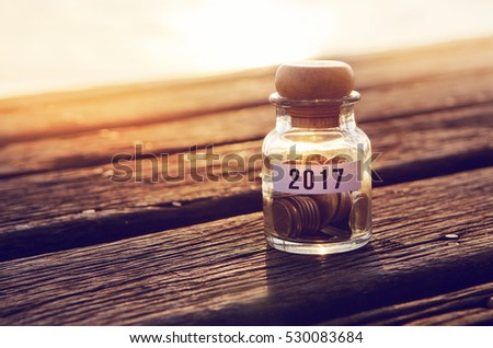 Coin in piggy bank with 2017 on paper, on table wood, Light and shadow, business and finance concept, copy space. retro filter effect.