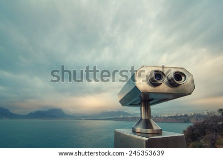 Coin Operated Binocular viewer next to the waterside promenade in Antalya looking out to the Bay and city. Landscape with beautiful cloudy sky, sea and mountains..
