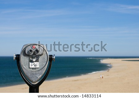 Coin operated binoculars for beach observation, blue sky and ocean, sandy beach
