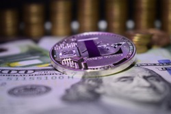 Coin physical Litecoin LTC, background from banknote and golden coins. Concept of cryptocurrency.