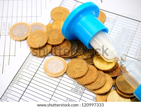 Coins and a sand-glass on documents.