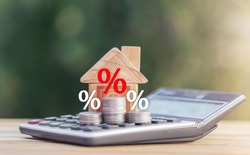 Coins and house  on the calculator And has an illustration of interest concept of calculating interest payments. planning savings money of coins to buy a home concept for property, mortgage, invest.
