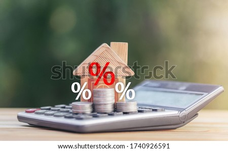 Coins and house  on the calculator And has an illustration of interest concept of calculating interest payments. planning savings money of coins to buy a home concept for property, mortgage, invest. Stock photo ©