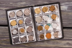 Coins collection on wooden desk. Top view flat lay.