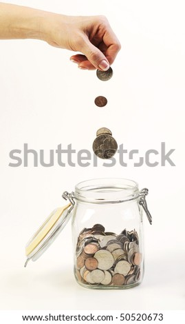 coins dropping in glass jar