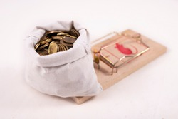 Coins in a white cloth bag, arranged in a mousetrap. A trap in the form of a large amount of coins. Light background.