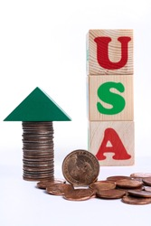 Coins in denominations of one American dollar, coins of a different denomination, the inscription USA made from letters on children's toy cubes on a white background