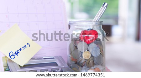 Coins in glass jar with Expenses word label on calendar. #1469774351