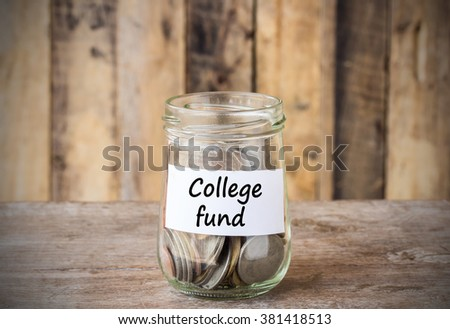 Coins in glass money jar with college fund label, financial concept. Vintage wooden background