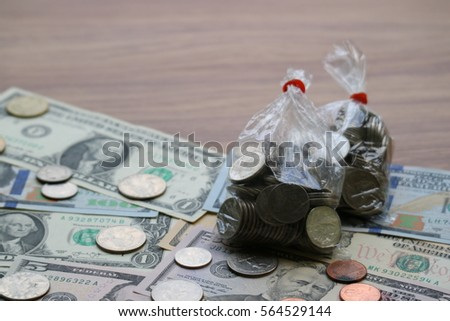 Coins in plastic bag on dollar banknote, finance saving investment concept