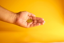 Coins in the hand. The concept of cheaper currency