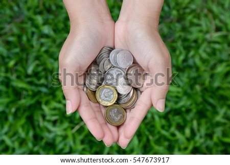 Coins in woman hand with green grass background - Saving money concept