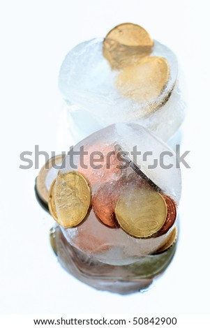 Coins inside ice cubes isolated on blue background