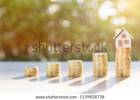 Coins on the wood and house in sunlight background present the savings money or investing to buy a home or loan. To buy a house or real estate or investment for the future. #1139828738