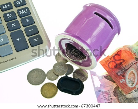 Coins out of pink piggy bank with banknote and calculator