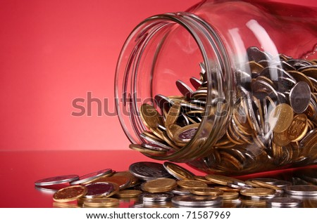 coins spilling from a money jar on red background