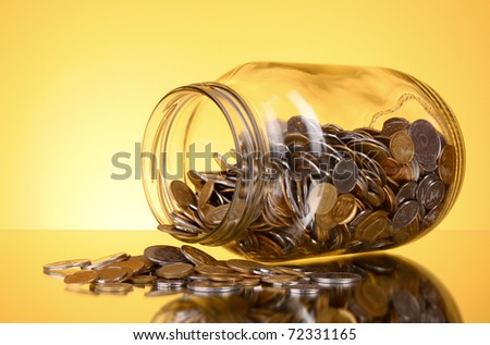 coins spilling from a money jar on yellow background
