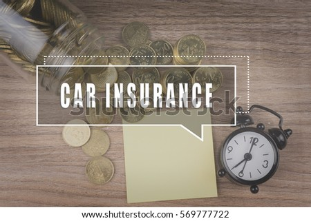 Coins spilling out of a glass jar on wooden background with CAR INSURANCE text . Financial Concept #569777722