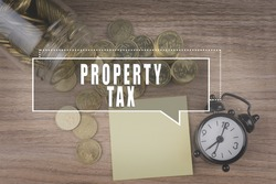 Coins spilling out of a glass jar on wooden background with PROPERTY TAX text . Financial Concept