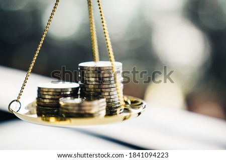 Coins stack with balance scale. Money management, financial plan, time value of money, business idea and Creative ideas for saving money concept.