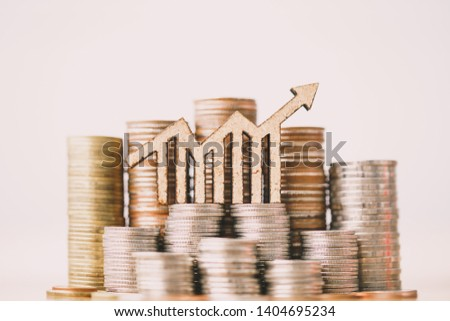 Coins stacking and wooden blocks arrow. Retirement planning. money saving and Investment concept. Business finance.  #1404695234