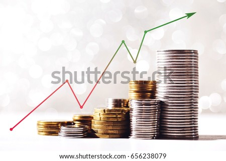 Coins stacks with a growth multicolor graph on silver sparkling bokeh background. Financial growth concept.