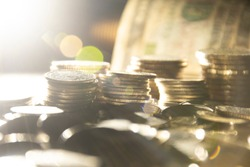 Coins with Banknote at background and backlight bokeh as for business finance concept background.