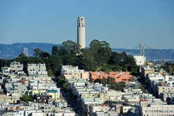 Coit Tower and the Bay Bridge as viewed from the intersection of Lombard & Hyde Street in San Francisco, California