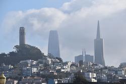 Coit Tower with a foggy San Francisco city skyline behind