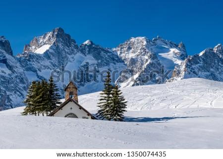 Col du Lautaret, Hautes-Alpes, Ecrins National Park, Alps, France: Winter view on the glaciers and mountain peaks (Gaspard Peak and La Meije) with La Chappelle des Fusillés