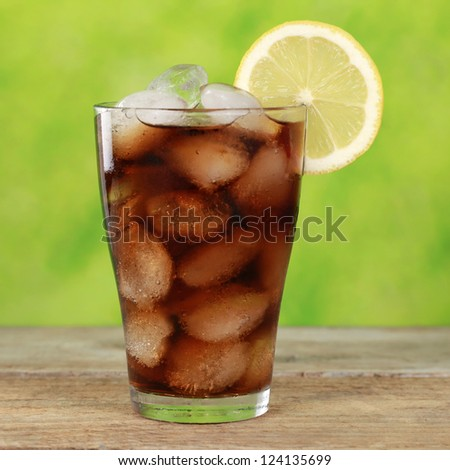 Cola drink in a glass with ice cubes, served with a slice of lemon - stock photo