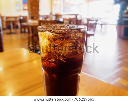 Cola glass soft drink with ice on wood table in restaurant background