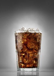Cola in a glass with ice cubes on the studio background