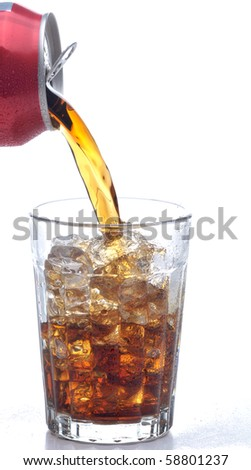 Cola pouring from a can into a glass filled with Ice. Over white background with water droplets on the table surface.
