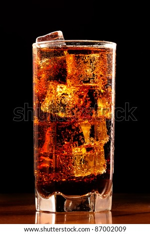 Cola with the ice on a table, glass, black background