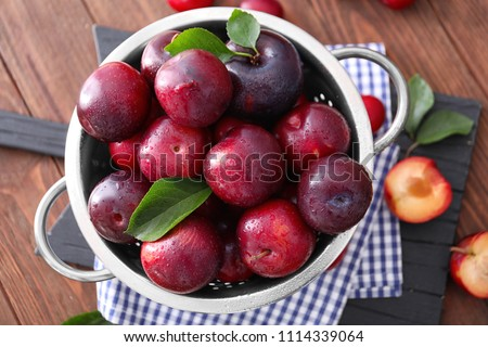 Colander with ripe juicy plums on table Foto stock ©