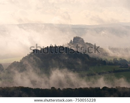 Cold and damp morning in autumn nature.  Outlines of forest hills hidden in thick mist. Unclear view to contours of hilly sides and peaks. #750055228