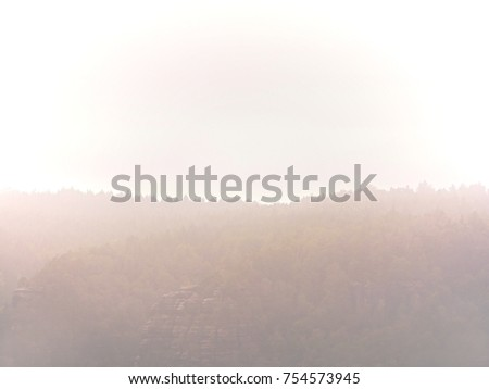 Cold and damp morning in autumn nature.  Outlines of forest hills hidden in thick mist. Unclear view to contours of hilly sides and peaks. #754573945
