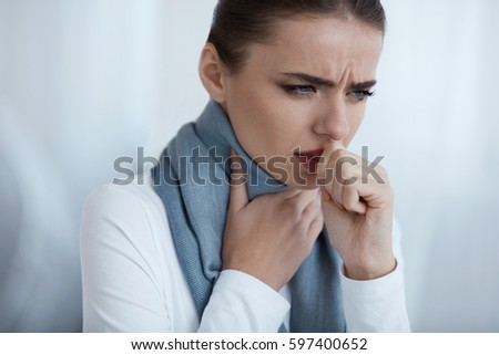 Cold And Flu. Portrait Of Beautiful Young Female With Cough And Sore Throat Feeling Sick Indoors. Closeup Of Ill Unhealthy Woman In Scarf Coughing, Caught Cold. Health Care Concept. High Resolution