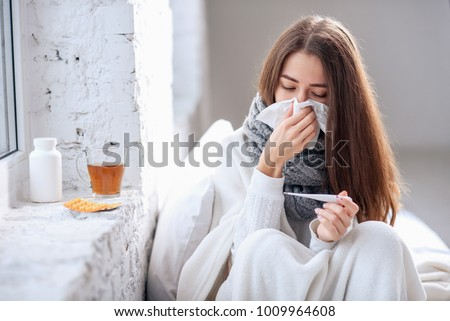 Cold and flu. Sick woman caught cold, feeling illness and sneezing in paper wipe. Closeup of beautiful unhealthy girl covered in blanket wiping nose and looking at thermometer. Healthcare concept. Stock photo ©